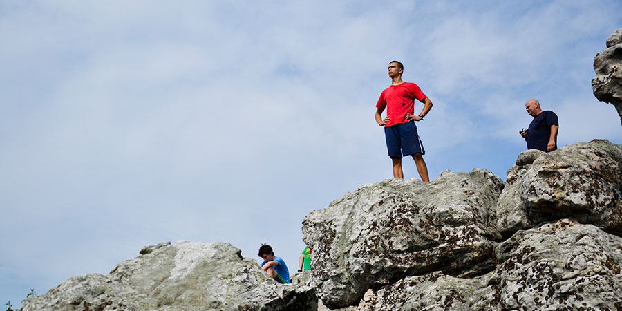 Young man looking into the distance from a rocky cliff