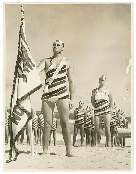 1935 sepia photo of North Bondi beach males in striped, full-body bathing costumes complete with bathing caps