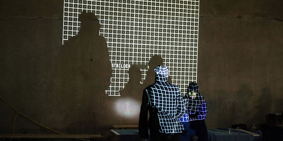 Two figures in a studio lit up by the screen display of a grid test pattern