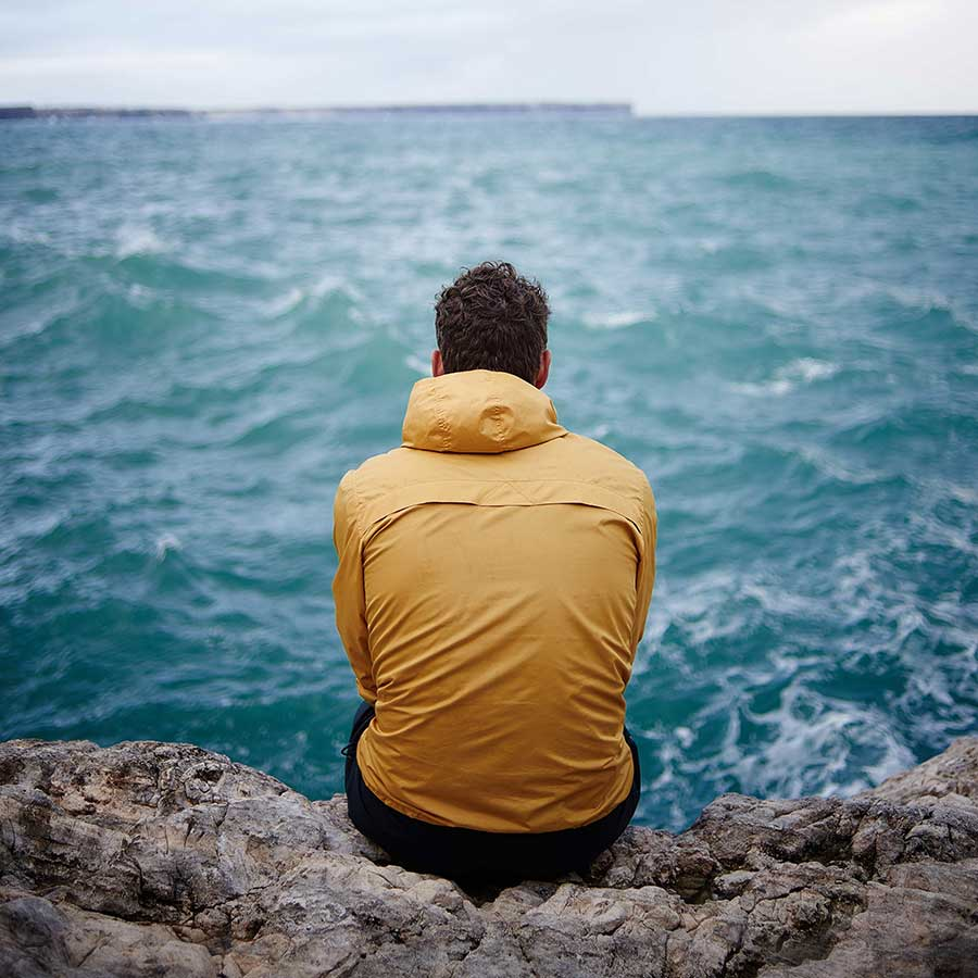 Adult male in a yellow windbreaker sitting on a rocky shore facing a rough sea.