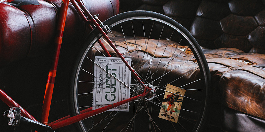 unsplash photo of a bicycle wheel and an old, worn, wrinkled sofa